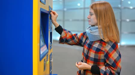 vending machine : Young Women is Buying a Ticket in Automatic Vending Machine, Paying by Coins and Taking her Tickets from Dispenser Stock Footage
