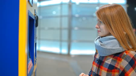 vending machine : Young Lady is Buying a Ticket in Automatic Vending Machine, Paying by Cash Money Bill