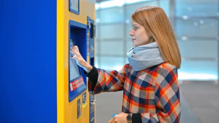 vending machine : Young Woman is Choosing a Ticket to Buy in the Automatic Vending Machine
