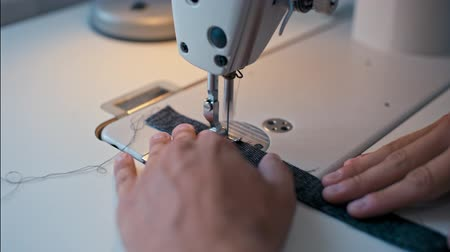 шов : CloseUp to Dressmaker Hands Working on Sewing Machine and Making Seam in Fashion Design Studio