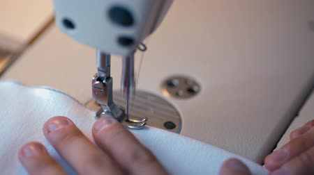 seams : CloseUp to Working Sewing Machine Making Seam on White Cloth in Fashion Design Studio