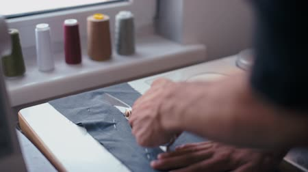 sewer : Tailor Man is Cutting Fabric by Professional Scissors in the Fashion Clothing Studio Stock Footage