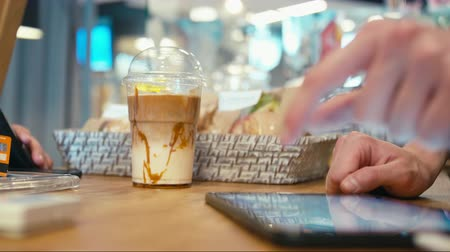 caramelo : Customer is Buying Takeaway Ice Latte Coffee and Paying by Credit Card in a Cozy Cafe Shop. CloseUp to Hands Vídeos