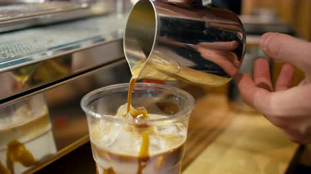 fagylalt : Barista is Pouring Coffee to Takeaway Cup Making Ice Cream Latte using Professional Machine in the Cafe Stock mozgókép