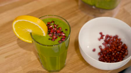 шпинат : Man is Pouring Spinach Smoothie to a Glass and Decorating Cocktail with Orange and Pomegranate Стоковые видеозаписи