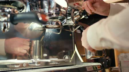 caffetteria : Barista è Foaming Milk di Steam nella Metal Jug mentre prepara Coffee Cappuccino nel caffè o nella caffetteria usando Professional Coffee Machine Maker