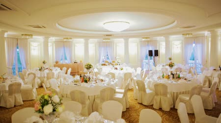 bouquets : Festive White Room with Dining Tables Decorated for Wedding Banquet Celebration in Hall Interior