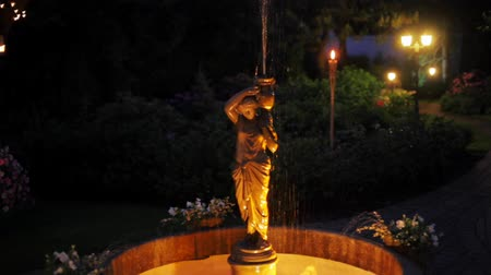 nocturnal : Antique Fountain with Luminous Statue of Stone Woman with a Vase in the Garden with Trees in Garlands in Night Stock Footage