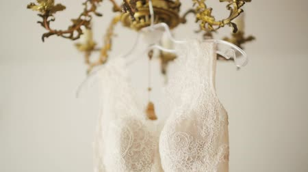 elegancia : Tilt Shot of a Cream White Wedding Lace Dress Hanging on a Gold Vintage Chandelier