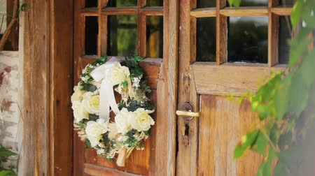 çelenk : Close-up Panning Shot of an Old Wooden Door with a Wreath of Flowers in a Rural Romantic House in the Countryside in Summer