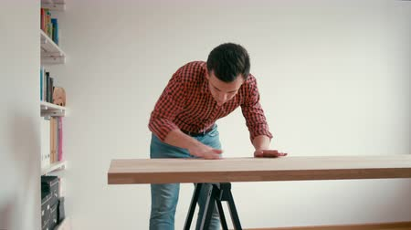 протирать : Long Shot of Young Man Making DIY Oak Wooden Table at Home. Man is Rubbing and Polishing Wood Desk with Sandpaper