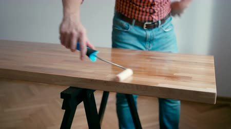 verificador : Craftsmanship and Woodwork: Carpenter Man in a Checkered Shirt is Finishing Wooden Oak Table with a Roller and Oil at Home