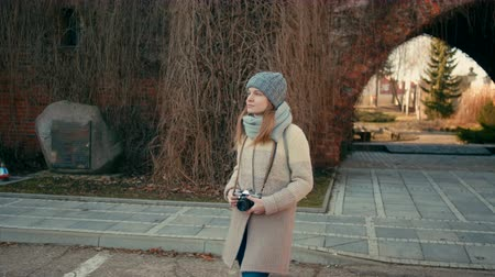 klimop : Medium Tracking Shot of a Young Tourist Woman Walking in the Old Ivy Arch in a Red Brick Castle with a Vintage Film Camera