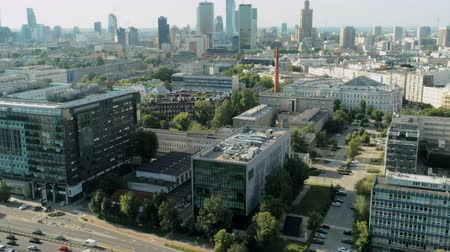 warszawa : Aerial View of Warsaw City with Skyscrapers, Palace and Office Buildings on Summer Day Zooming Out to Multi-lane Road with many Cars in Traffic Jam near Green Park. 4K Drone Fly backward Shot