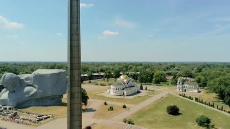 запомнить : Brest Hero Fortress - WWI and WWII Memorial Complex with Metal Obelisk, Main Courage Monument and Orthodox Church in Belarus in Summer. 4K Aerial View, Zoom Out Shot Стоковые видеозаписи