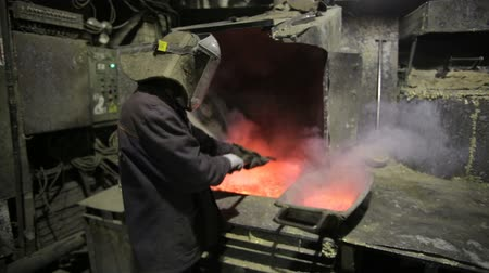 brickwall : Hard work in the foundry, worker controlling iron smelting in furnaces, too hot and smoky working environment