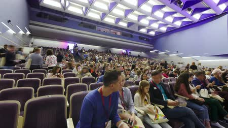 coming : NOVOSIBIRSK, RUSSIA - MAY 7, 2018: crowd coming to conference large hall, sitting on the places, talking, meeting, and waiting start of seminar. Big education performance from economic experts Stock Footage