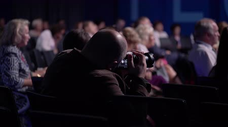 listener : A professional photographer taking photos at press conference or seminar in auditorium. Businessmans on the training from experts in management and marketing listening the coach speech at background