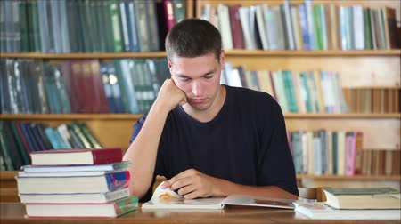 jovem : tired student in the library reading books