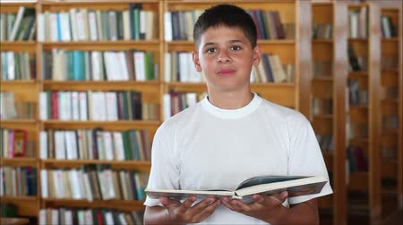 posando : schoolboy in the library looking at the camera and smiling