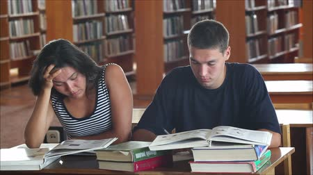 učit se : tired students in the library reading books