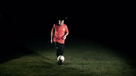 buty sportowe : Male soccer player juggling the ball in black background slow motion Wideo