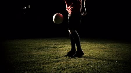 jogador de futebol : Player kicking a soccer ball on field over black background slow motion