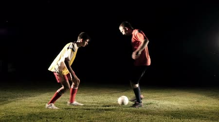 Duel of football players at soccer ball stadium at night slow motion