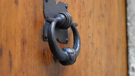 bater : Arty looking historic forged metal round door handle on an old oak door  touched and knocked by a female hand in Prague in a sunny day in autumn. The door handle looks medieval and unusual