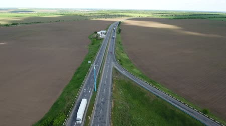 záběry : Wonderful aerial shot of a country highway with moving cars and trucks and wide green agricultural fields stretching nearby. The landscape and skyscape look great and gorgeous. Dostupné videozáznamy