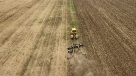 глыба : Amazing aerial shot of a big tractor drawing a spike and a disc harrows to remove wheat straw and to do a  tillage in Eastern Europe in a sunny day in summer. The drone is flying after the tractor Стоковые видеозаписи
