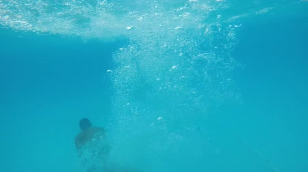 plunging : An inspiring view of a young man in multicolored shorts plunging in the turquoise waters of the swimming pool in summer in slow motion Stock Footage