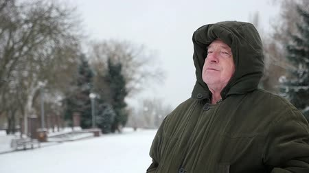 good new year spirit : An original view of an old man with an anorak hood on his head who sits on an alley bench and looks up in winter in slo-mo. Stock Footage