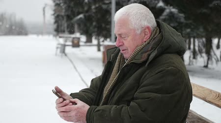 good new year spirit : An original view of an old wise man dressed in a dark green anorak who sits on an alley bench and looks at his mobile in winter in slo-mo.