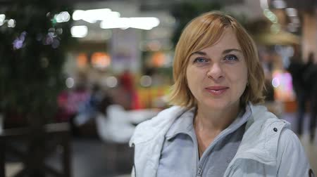 bob hairstyle : A cheery view of a smiling blond woman who stands and smiles in a local shopping mall. She is in a white jacket and grey zip up Tshirt.