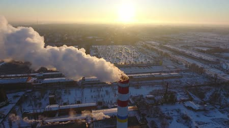 морозный : A bird`s eye view of a soaring chimney with a slow stream of smoke at a wonderful sunset in winter. It stands among snowy houses. Стоковые видеозаписи