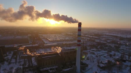 zimní : A bird`s eye view of a sky-high chimney with a slow flux of smoke at a wonderful sunset in winter. It stands near a plant. and houses. Dostupné videozáznamy