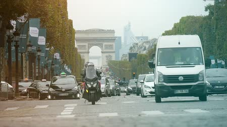 arch of triumph : Paris, France - November 3, 2017:An inspiring view of the Arc de Triomphe in Paris in autumn in slo-mo. The highway leading to it is full of cars on a sunny day in autumn.