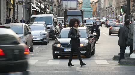 chique : Paris, France - November 6, 2017:An optimistic view of a funny woman with lush and airy hairstyle going on a crosswalk in slow motion. She enjoys the life in Paris in autumn.