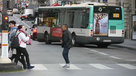 šik : Paris, France - November 6, 2017:An unusual view of elegant people going on a crosswalk in slow motion. A lot of motorbykes move in the frontground in Paris in slow motion.
