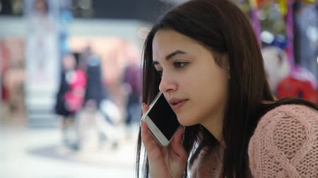 supermarket food : Profile of a beautiful young woman with long loose hair keeping a smartphone and talking to her cutie boy in a supermarket. She looks optimistic Stock Footage