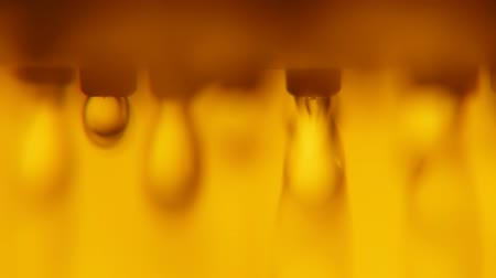 radiante : An optimisti macro shot of radiant dribs of water trinkling from a modern metallic spray in  a bathroom with yellow and golden walls.