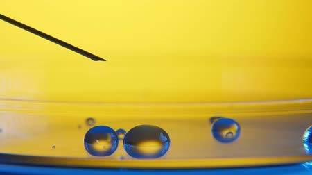 původní : An arty closeup of falling water drops plashing on a crystaline surface in a modern medical laboratory with yellow walls.