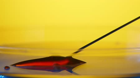 plash : A striking view of a red blood puddle on a flat and glassy surface. A metallic needle pulls in blood in the medical laborator with yellow walls. Stock Footage