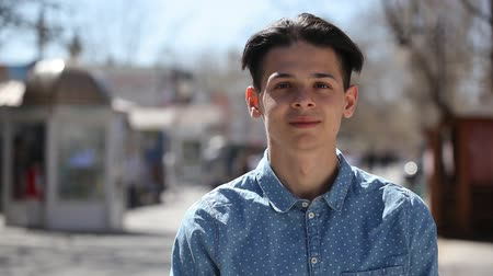 arejado : Bokeh portrait of an optimistic young man with crew haircut smiling happily and standing in a city street on a sunny day in spring Vídeos