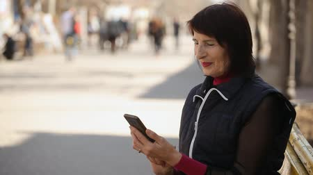 ищу : Bokeh profile of a smart woman with a bob haircut sitting on a bench and touching the screen of her mobile in the sunny alley in spring Стоковые видеозаписи