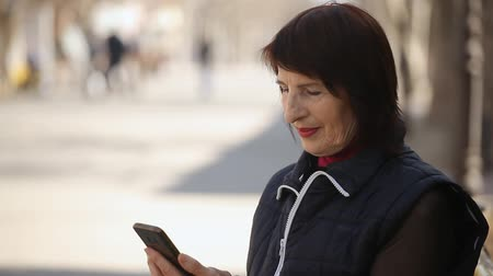 впечатляющий : Bokeh profile of a snappy woman with a bob haircut sitting on a bench and touching the screen of her mobile in the nice alley in spring