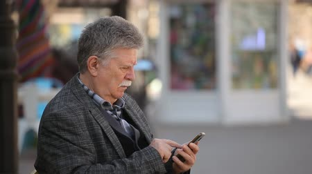 sokak lâmbası direği : Bokeh profile of a smart senior man with a mustache browsing the net on his smartphone in the nice alley on a sunny day in spring.
