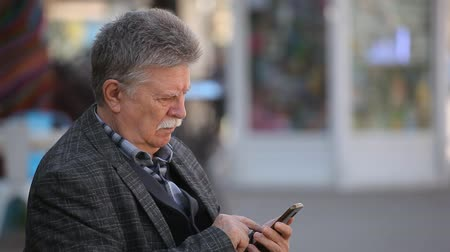 sokak lâmbası direği : Bokeh portrait of a confident senior man with a mustache surfing the net on his smartphone in an alley on a sunny day in spring.