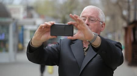 vrásčitý : An impressive view of a wise senior taking a selfie in an airy alley on a sunny day in spring. He feels cheerful and confident. Dostupné videozáznamy